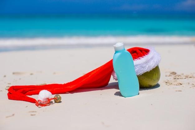 Suncream en santa hat op kokosnoot op wit exotisch strand