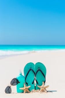 Suncream-fles, slippers, zeesterren en zonnebril op wit zandstrand met uitzicht op de oceaan
