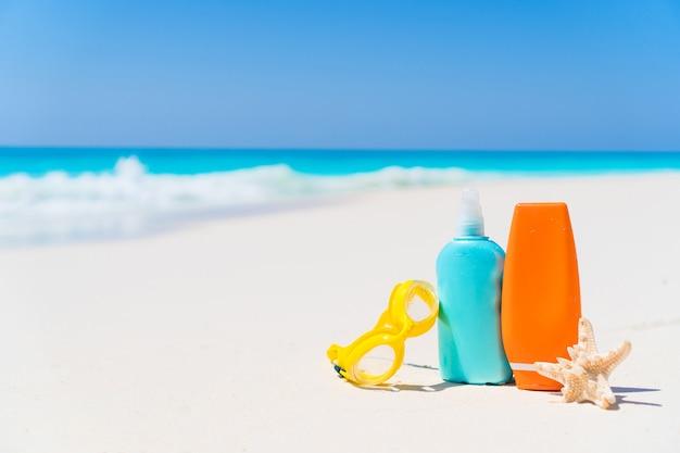 Suncream-flessen, bril, zeester op wit zandstrand met uitzicht op de oceaan