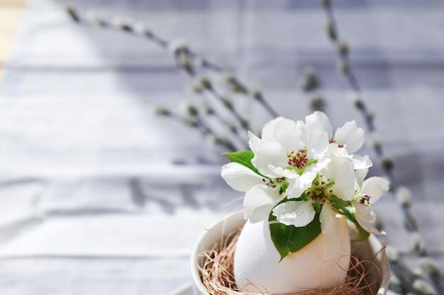 Sunny easter-samenstelling van wilgentakken en natuurlijke bloemen in een wit ei in een cirkel op grijs tafelkleed.