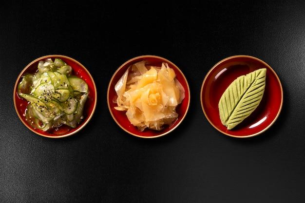 Sunomono, gember en wasabi geïsoleerd op zwarte achtergrond. bovenaanzicht.