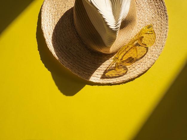 Sunprotection-objecten. de hoed van de strovrouw met gele zonglazen op gele mening