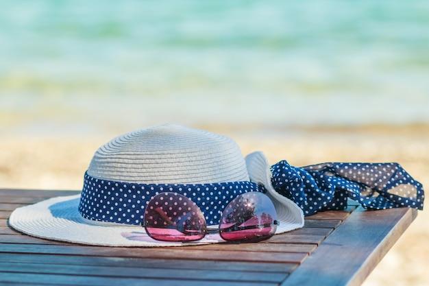 Sunprotection-voorwerpen op het strand in vakantiezonnebril en witte hoed.