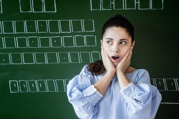 Supdrised meisje in glazen blijft in de buurt van schoolbord in de klas