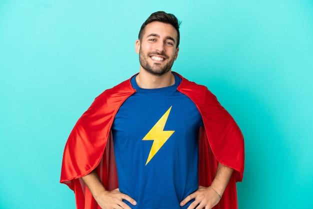 Super held blanke man geïsoleerd op blauwe achtergrond poseren met armen op heup en lachend