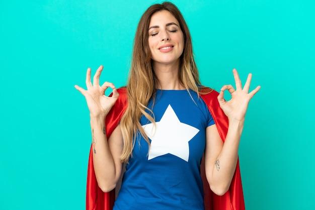Super held blanke vrouw geïsoleerd op blauwe achtergrond in zen pose