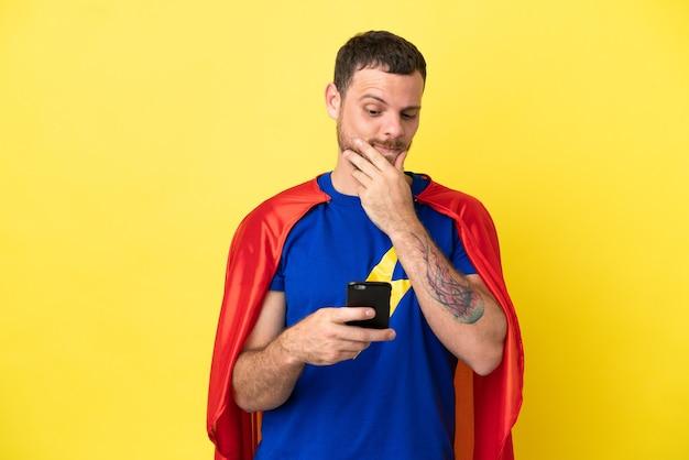 Super held braziliaanse man geïsoleerd op gele achtergrond denken en een bericht verzenden