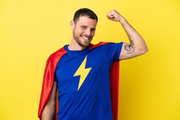 Super held braziliaanse man geïsoleerd op gele achtergrond doet sterk gebaar