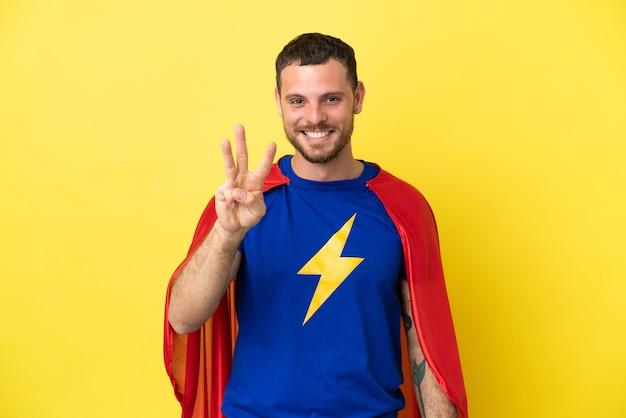 Super held braziliaanse man geïsoleerd op gele achtergrond gelukkig en drie tellen met vingers
