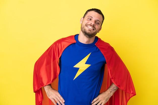 Super held braziliaanse man geïsoleerd op gele achtergrond poseren met armen op heup en lachend