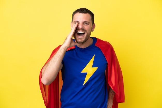 Super held braziliaanse man geïsoleerd op gele achtergrond schreeuwen met mond wijd open