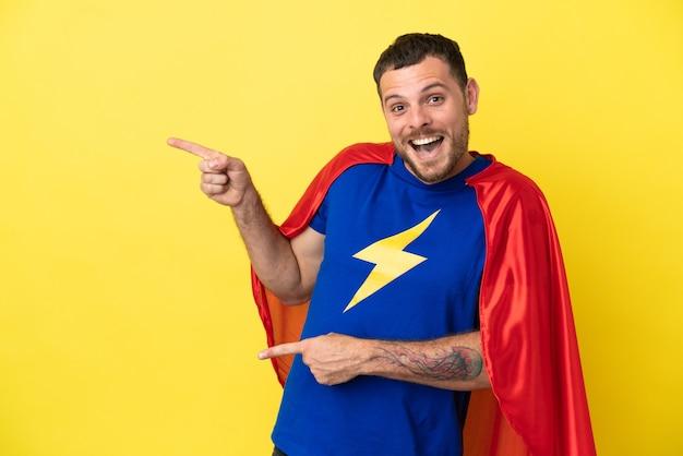 Super held braziliaanse man geïsoleerd op gele achtergrond verrast en wijzende kant