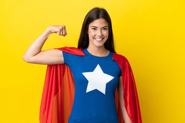 Super held braziliaanse vrouw geïsoleerd op gele achtergrond doet sterk gebaar