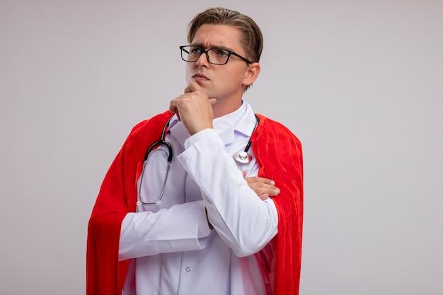 Super held dokter man met witte jas in rode cape en bril met stethoscoop om nek opzij kijken met hand op kin met peinzende uitdrukking op gezicht denken staande over witte muur