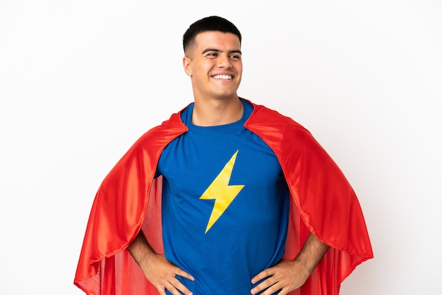 Super held over geïsoleerde witte achtergrond poseren met armen op heup en lachend