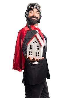 Super held zakenman bedrijf een klein huis