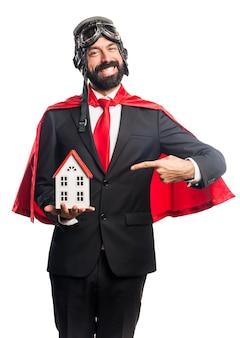 Super held zakenman bedrijf een klein huis Gratis Foto