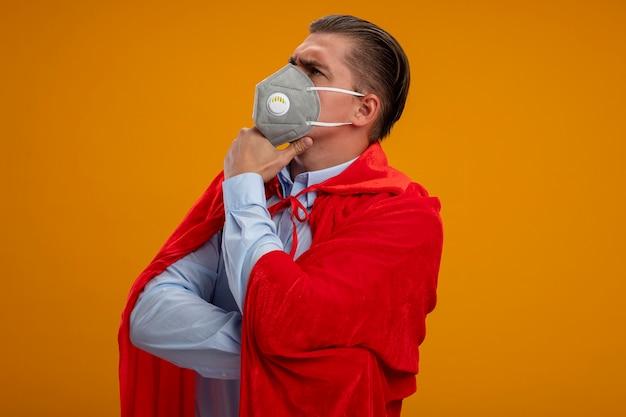 Super held zakenman in beschermend gezichtsmasker en rode cape opzij kijken met hand op kin denken met serieuze blik staande over oranje achtergrond