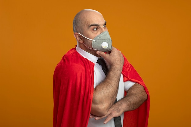 Super held zakenman in beschermend gezichtsmasker en rode cape opzij kijken met peinzende uitdrukking op gezicht met hand op kin denken