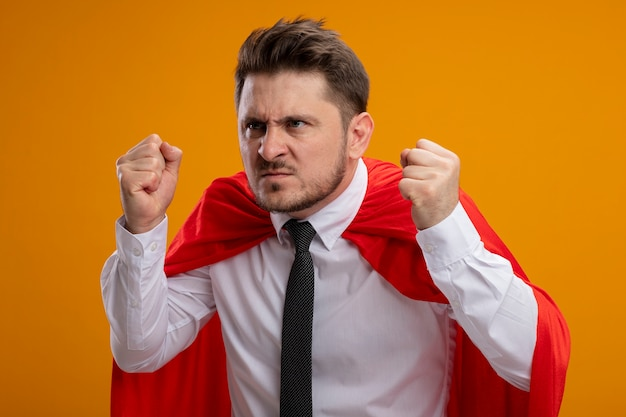 Super held zakenman in rode cape balde vuist met boos gezicht staande over oranje muur