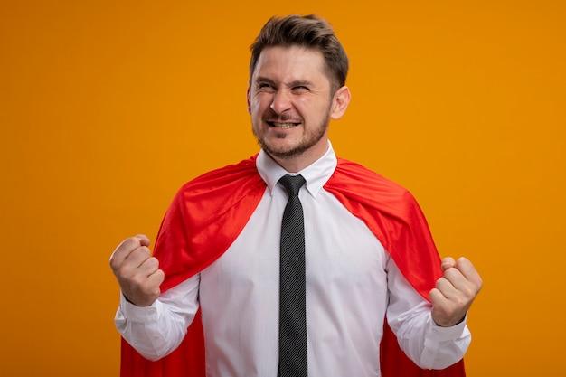 Super held zakenman in rode cape balde vuisten blij en opgewonden staande over oranje muur