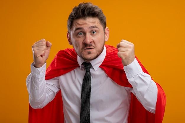 Super held zakenman in rode cape balde vuisten met boos gezicht staande over oranje muur
