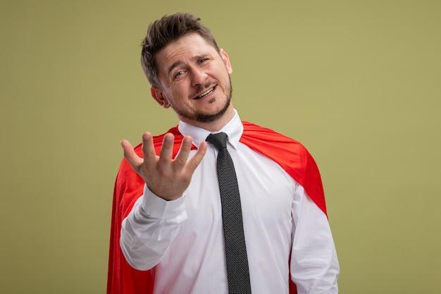 Super held zakenman in rode cape camera kijken met armen lachend met blij gezicht staande over groene achtergrond