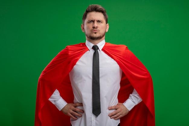 Super held zakenman in rode cape camera kijken met ernstige zelfverzekerde uitdrukking met armen op heup staande over groene achtergrond