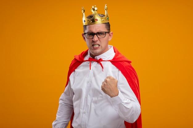Super held zakenman in rode cape en bril dragen kroon camera kijken met agressieve expressie balde vuist permanent over oranje achtergrond