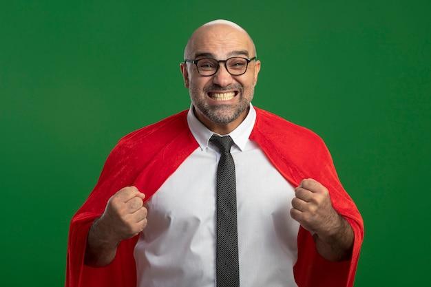 Super held zakenman in rode cape en glazen balde vuist blij en opgewonden staande over groene muur
