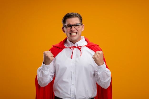 Super held zakenman in rode cape en glazen balde vuisten met een boos gezicht gaan wild staande over oranje muur