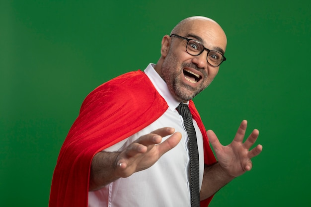 Super held zakenman in rode cape en glazen blij en opgewonden met armen kijken naar voren staande over groene muur