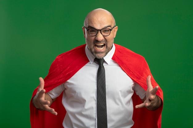 Super held zakenman in rode cape en glazen schreeuwen en schreeuwen met opgeheven armen gefrustreerd en boos staande over groene muur