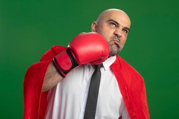 Super held zakenman in rode cape en in bokshandschoenen zichzelf ponsen