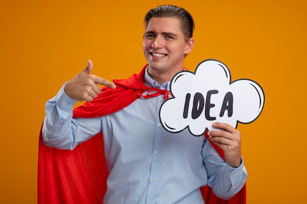 Super held zakenman in rode cape houden toespraak bubble bord met woord idee wijzend met wijsvinger naar het glimlachend staande over oranje achtergrond