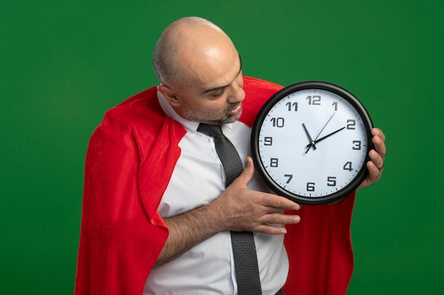 Super held zakenman in rode cape houden wandklok kijken naar gek verbaasd en verrast staande over groene muur