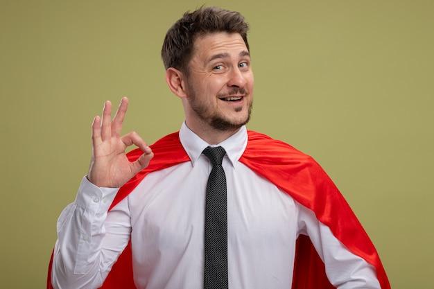Super held zakenman in rode cape kijken camera glimlachend blij en positief weergegeven: ok teken staande over groene achtergrond