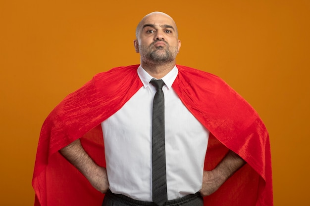 Super held zakenman in rode cape kijkt zelfverzekerd met armen naar heup staande over oranje muur