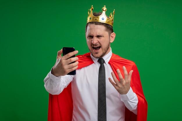 Super held zakenman in rode cape kroon dragen met behulp van smartphone kijken naar scherm gaan wild gek boos staande over groene achtergrond