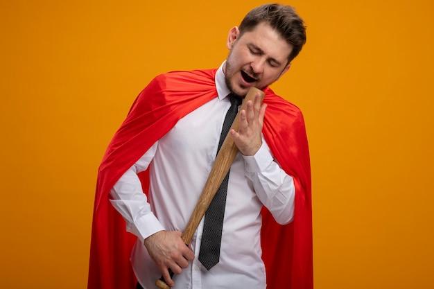 Super held zakenman in rode cape met honkbalknuppel gebruiken als microfoon zingen staande over oranje achtergrond