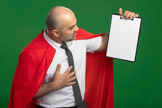 Super held zakenman in rode cape met klembord met blanco pagina's kijken geïntrigeerd
