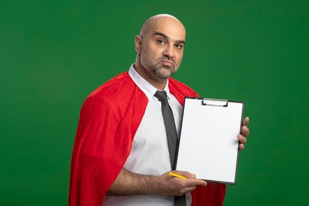 Super held zakenman in rode cape met klembord met blanco pagina's met ernstig gezicht