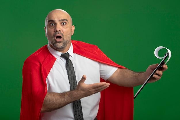 Super held zakenman in rode cape met klembord met blanco pagina's wijzend met arm op klembord met verwarring uitdrukking staande over groene muur