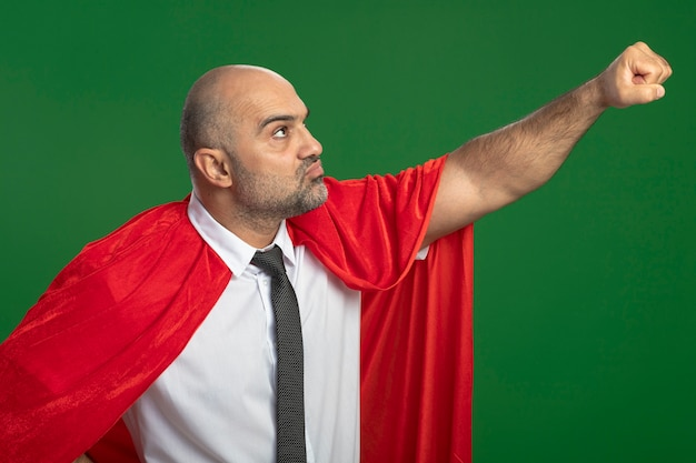 Super held zakenman in rode cape opzij kijken arm in vliegende gebaar houden klaar om te helpen kijken zelfverzekerd staande over groene muur