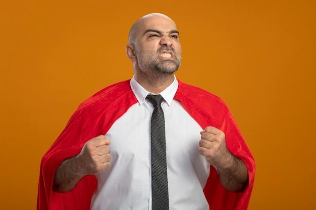 Super held zakenman in rode cape opzij kijken balde vuisten met boze agressieve uitdrukking staande over oranje muur