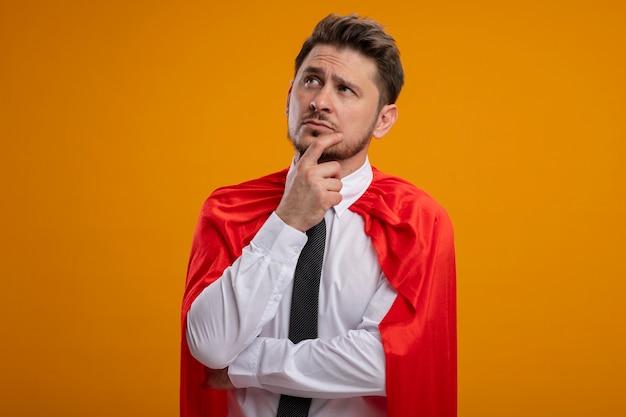 Super held zakenman in rode cape opzij kijken met peinzende uitdrukking denken staande over oranje achtergrond