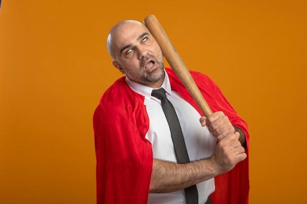 Super held zakenman in rode cape ponsen zichzelf met honkbalknuppel