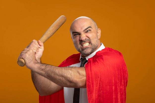 Super held zakenman in rode cape swingende honkbalknuppel met boze agressieve uitdrukking wild staande over oranje muur