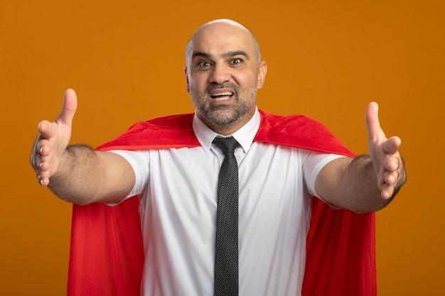 Super held zakenman in rode cape voorzijde glimlachend vriendelijk verwelkomend gebaar met handen permanent over oranje muur kijken kijken