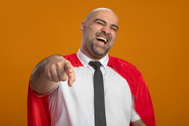 Super held zakenman in rode cape wijst naar je lachend staande over oranje muur